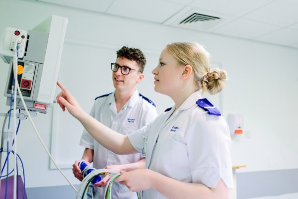 A male and female student nurse operating some equipment on a ward. Photograph by Mark Webster