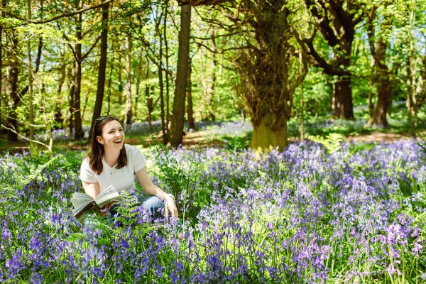 Student on a field trip crouching in wild bluebells in a woodland.