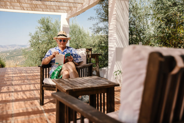 Man reading a book under a terrace in Spain