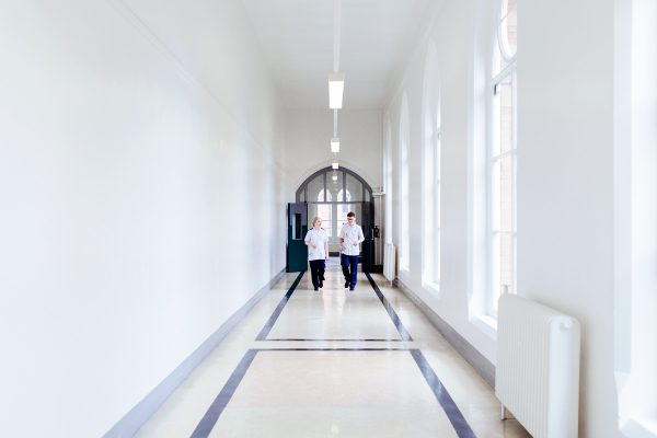A male and female student nurse walking down a corridor. Photograph by Mark Webster