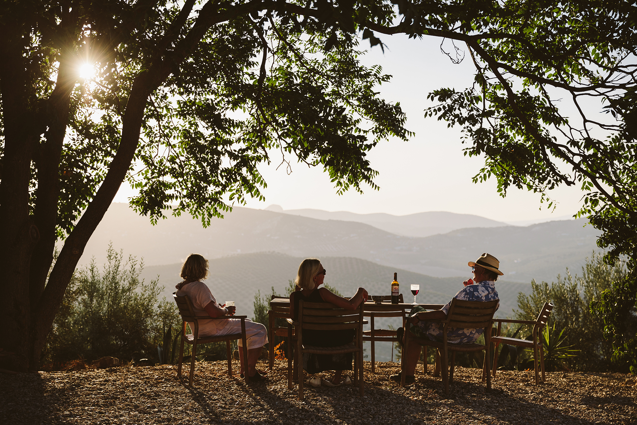 Three people sitting at a table during sunset in Spain